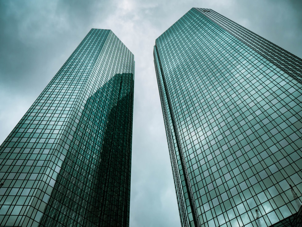 two high-rise buildings under gray clouds during daytime