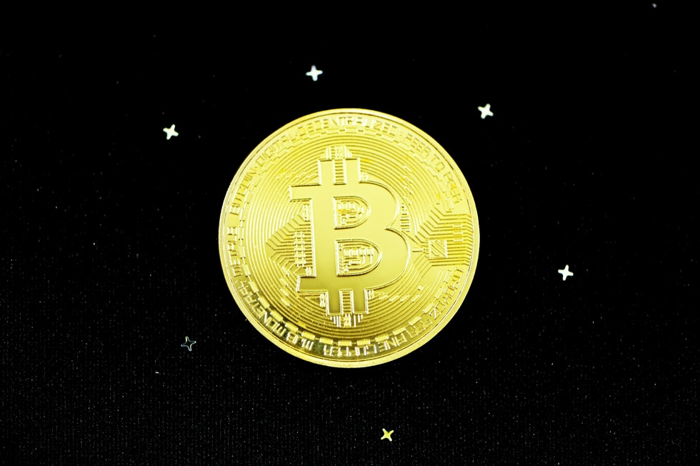 gold round coin on black textile