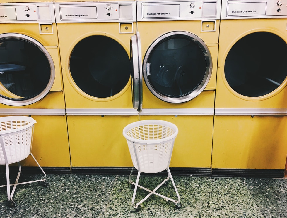 white plastic laundry basket beside yellow front load washing machine